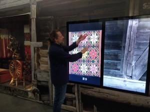 Utstillingens fagkonservator demonstrerer en av de interaktive skjermene. Her var det vist en rekke draktdeler og tekstiler. Ved å berøre skjermen kan man forstørre hver del så mye at man kan se selv små detaljer i mønsteret.